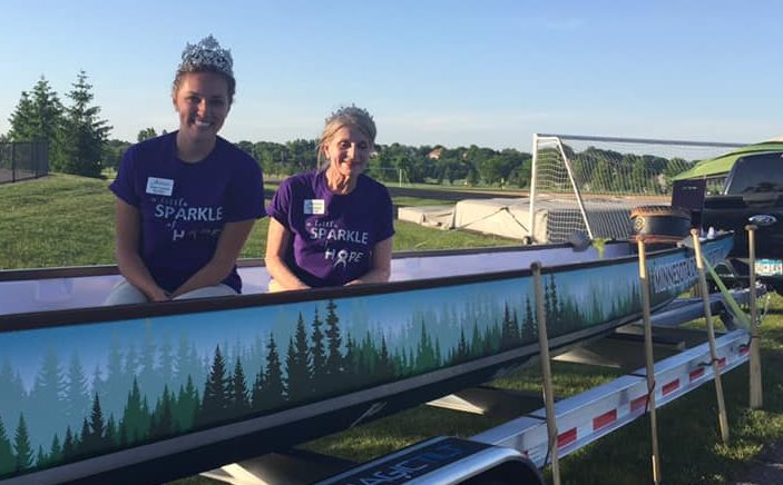 Two female-presenting people in dragon boat wearing tiaras at the South Washington County Relay for Life
