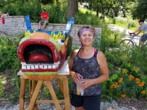 Nancy standing by dragon boat head at Phalen Park