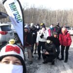 MNDBC Team members pose by our new teardrop banner with our logo as we enjoy beverages in the parking lot of the Richardson Nature Center in Bloomington MN. Packed snow covers the pavement, and leafless trees are in the background.