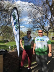 Two MNDBC club members stand near our teardrop banner in a park next to an amphitheater brick wall. Green grass and blue sky in the background.