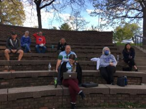 People are sitting in an amphitheater, socially distanced, looking towards the camera